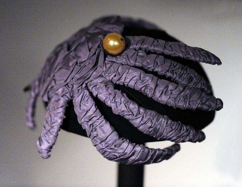 Die extravagante violette Hutspange, verziert mit einer Perle, wirkt mit ihrer fast spinnenartigen Form eher wie ein Kopfputz als eine schützende Kopfbedeckung. Foto: Jürgen Hoffmann © LVR-Industriemuseum