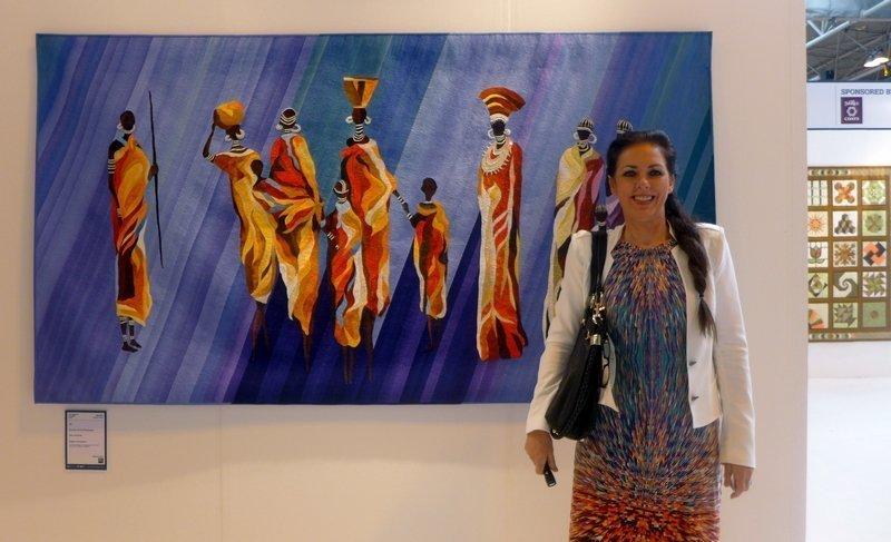Janneke de Vries-Bodzinga neben ihrer Arbeit Poor and Rich Gewinner in der Kategorie Pictorial Quilts