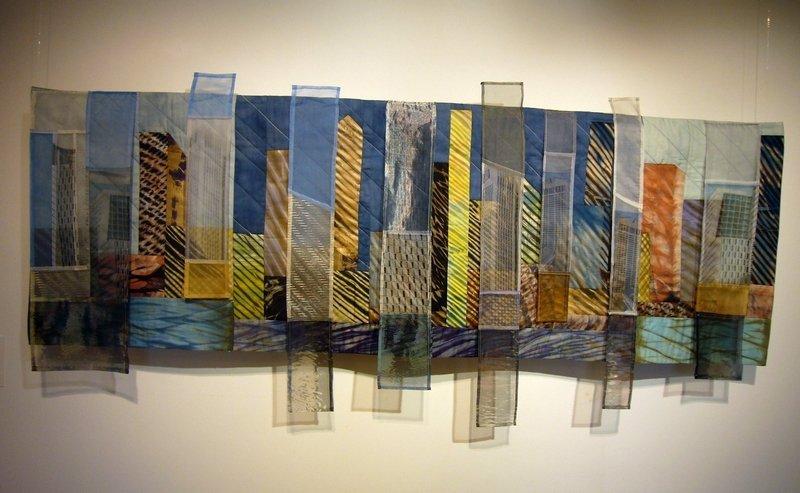 Bärbel Grünewald: Skyline, 2013, 150 x 150 cm Hochhäuser türmen sich im schräg einfallenden Licht zu einer Skyline am Fluss. Silbern schimmernde Hochhausfassaden verstärken den luftigen und durchsichtigen Eindruck.