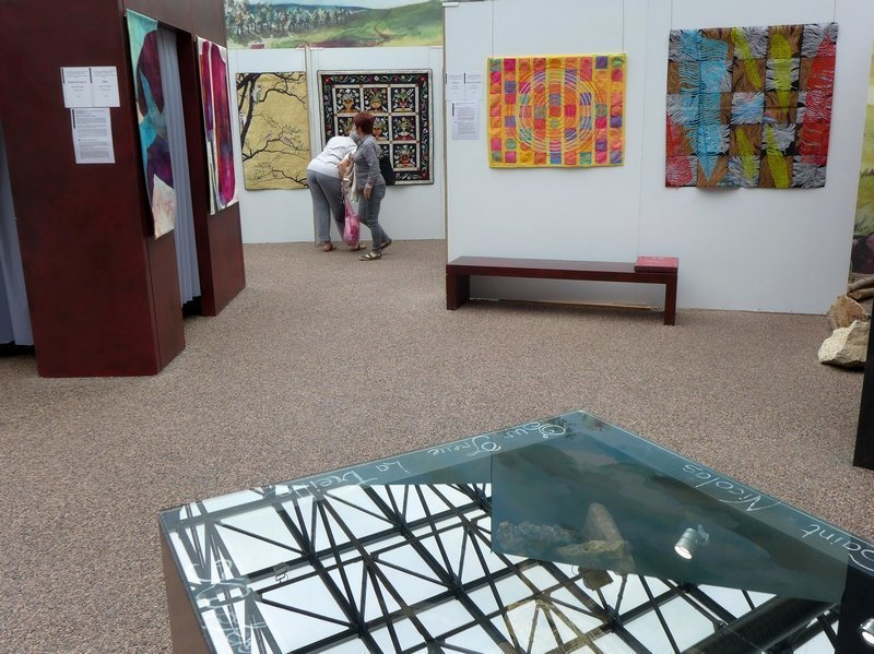 Blick in die Ausstellung 'Das Europäische Patchwork Treffen und seine Künstlerinnen von 1994 bis 2014′ im Hintergrund rechts zwei Arbeiten von Jane Lloyd (UK): Whirlpool, 2000 (li), Macaws flew overhead, 2008 (re)