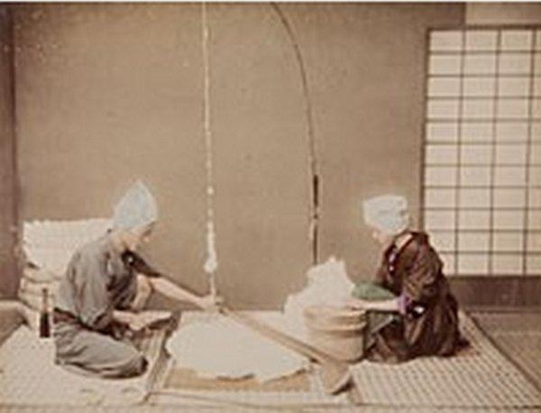 Bearbeitung roher Baumwolle: Die Frau rechts trennt die Fasern von den Samen, der Mann links lockert sie zum Spinnen auf Studio Kusakabe Kimbei, ca. 1890-99, Albuminabzug, handkoloriert MOK, P 9, copyright Rheinisches Bildarchiv
