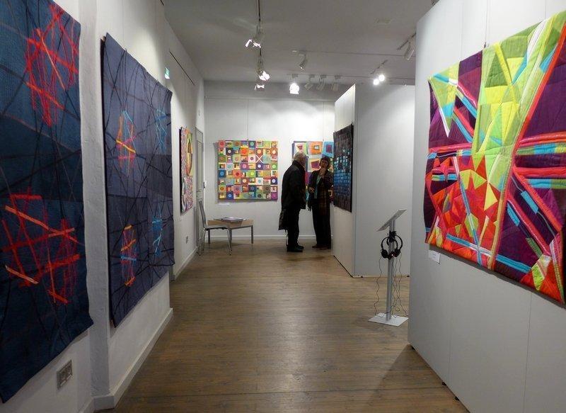 Arbeiten von Randa Stewner (li), Arlette Schnabl: Kromatom (re), li im Hintergrund Arbeit von Gabriele Schultz-Herzberger Ausstellung 'Musik trifft Stoff' - Network Quilters