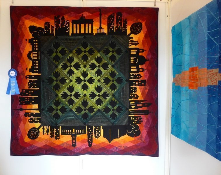 Claudia Scheja: Skyline, 175 x 175 cm (li), Marina Hilgert-Vervoort: Blockade, 80 x 119 cm Ausstellung 'WQC Quilts 2014'