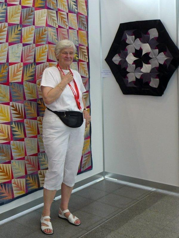 Brigitte Morgenroth vor ihrem Quilt 'Weitverzweigt', 146 x 218 cm, rechts daneben: 'Nie wieder - oder doch?', 100 x 87 cm  Ausstellung 'Log Cabin - heute'