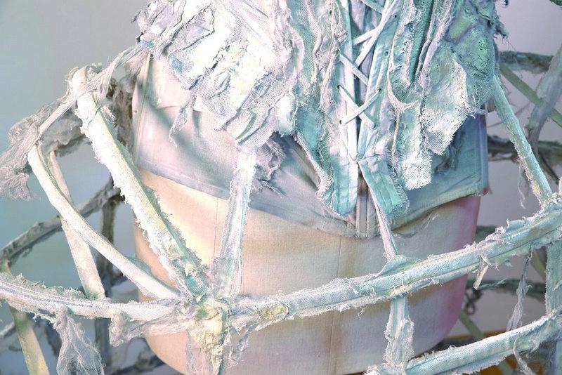 Ausstellung 'Die Kleider der Buhlschaft' Ulrike Folkerts, Tod, 2005, Detail Foto: ©Anneliese Kaar, Salzburg Detail des von barocken Schnittformen inspiriertes Kostüms. Reifrock aus Miederstäben in Schläuchen aus grau gefärbten Köperbändern. Mit zerrissenem Seidentüll besetzt, Ton in Ton gefärbt, bemalt in fahlem Weiss. Schulterfreies Miederoberteil mit Stäbchen aus Baumwolle, grau gefärbt und mit zerrissenem Seidentüll besetzt und bemalt. Kostüm: Dorothea Nicolai Schuhe: Barockschuhe aus Leder mit Metallschliesse, grau und bemalt.