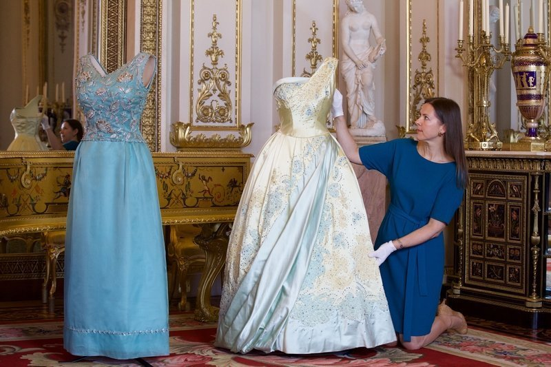 Kuratorin Caroline de Guitaut arrangiert ein blass blau-goldenes Abendkleid von Sir Norman Hartnell, das die Queen anlässlich eines Staatsbesuchs in den Niederlanden 1958 trug, für eine Preview der Ausstellung im White Drawing Room, Buckingham Palace. Links das türkise Seidenkleid mit silbernen floralen Stickereien von Hardy Amies, das die Queen für das offizielle Portraitfoto von Cecil Barton (oben) 1968 trug. Senior Curator of Decorative Arts, Caroline de Guitaut arranges a pale blue and gold evening dress by Sir Norman Hartnell, worn by The Queen on a State Visit to The Netherlands in 1958 at a preview of Fashioning a Reign in the White Drawing Room, Buckingham Palace. Fashioning a Reign at the Summer Opening of the State Rooms, Buckingham Palace opens on 23 July 2016. Royal Collection Trust / © Her Majesty Queen Elizabeth II 2016