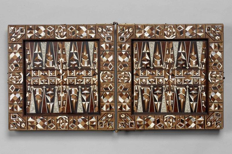 Spielbrett für Mühle, Schach und den 'Langen Puff' (Ausschnitt), Augsburg, vor 1596 Die Intarsien aus Obstbaumholz, Ebenholz, Elfenbein und Perlmutt zeigen ein komplexes Muster aus geometrischen Körpern. Polyeder gelten in der Renaissance als besondere Herausforderung im Kunsthandwerk. Das hier verwendete Muster geht wohl auf die Holzschnittserie 'Geometria et Perspectiva' (1567) von Lorenz Stoer zurück. © KHM-Museumsverband Foto freundlicherweise vom Museum zur Verfügung gestellt