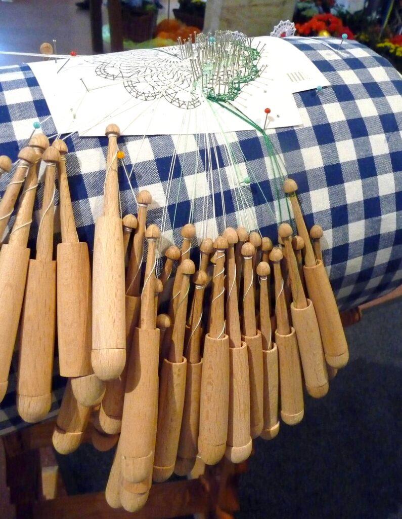 Klöppelkissen mit Klöppelbrief, angefangener Spitze und herunterhängenden Klöppeln. Foto: Fränkischer Klöppelverband Foto freundlicherweise vom Pfalzmuseum Forchheim zur Verfügung gestellt