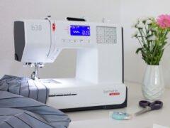 Eingeschaltete Nähmaschine neben Blumenstrauß