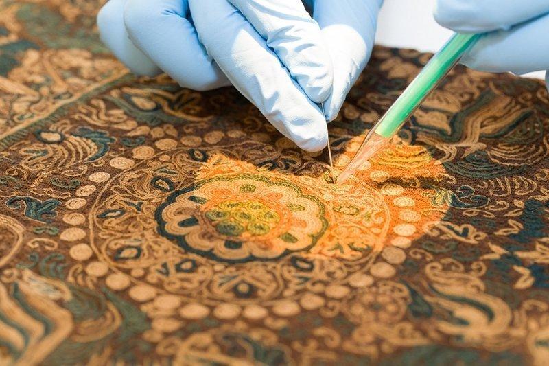 Reinigung Mit einer winzig kleinen Staubsaugerdüse wird die Stickerei von Schmutz (Staub, Verkrustungen, Insektenrückstände, Schimmel) befreit. © Abegg-Stiftung, CH-3132 Riggisberg (Foto: Christoph von Viràg) Foto freundlicherweise vom Museum zur Verfügung gestellt