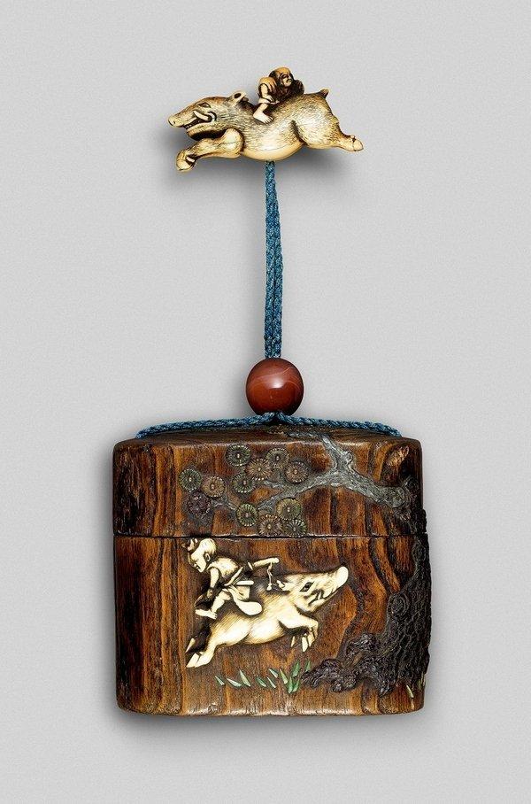 Ein Vasall reitet rückwärts auf einem galoppierenden Eber. Gleiches Motiv auf Tonkotsu, Kiri-Holz mit Elfenbein-Relief und Netsuke aus Elfenbein. Japan, Edo-Zeit (1602–1868). Foto: Jean Marie Colrat, St. Gratien Foto freundlicherweise vom Museumsdienst der Stadt Köln zur Verfügung gestellt