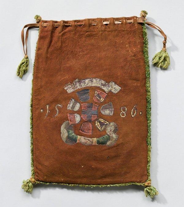 Archivsäcklein mit einem Wappenkreis Das Archivsäckchen ist mittig mit einem Wappenkreis bemalt, der das Schweizer Kreuz (rotes Schild mit durchgehendem silbernen Kreuz) umschliesst. Im Uhrzeigersinn, von der oberen Mitte beginnend, sind die Wappen von Bern, Luzern, Uri, Schwyz, Solothurn oder Unterwalden, Zug und Freiburg dargestellt. Zwei den Wappen entspringende Arme vereinen sich unter dem Wappenkreis zu einem Handschlag. In diesem Archivsäckchen waren vermutlich Urkunden, die im Zusammenhang mit den Kantonen der Schweiz standen, verwahrt. Freiburg i. Üe., 1586; bemaltes Leder, lederne Zugschnüre und Zierknoten, seidene Fransenborten und Quasten, 46 x 36 cm; Staatsarchiv Freiburg, Archivsäcklein, 8 © Abegg-Stiftung, CH-3132 Riggisberg Foto: Christoph von Viràg, freundlicherweise von der Abegg-Stiftung zur Verfügung gestellt