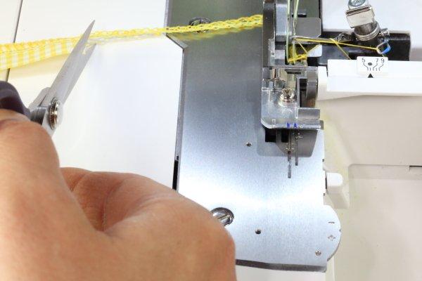 Sowohl die Anfangskette wie auch die Endkette bis zur Stoffkante zurückschneiden.