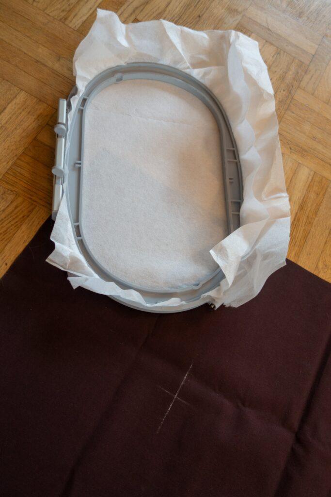 Reißvlies in ovalen Stickrahmen eingespannt