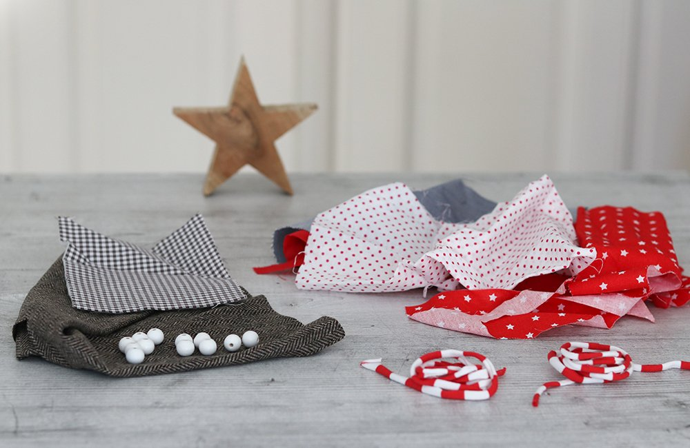 Fabric remnants and beads in Christmas-y red and natural colors