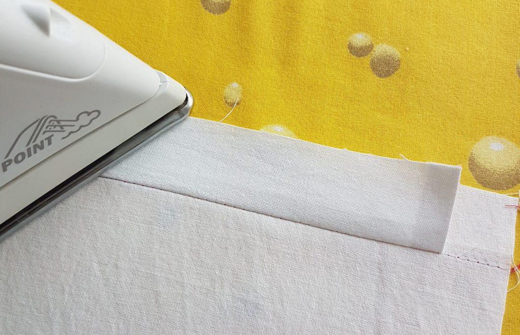 Behelfsmasken nähen mit der Overlock – Streifen zur Stoffkante bügeln
