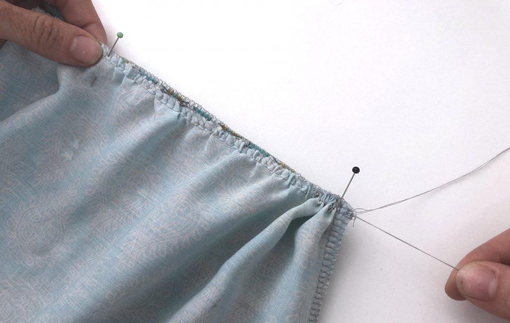 Bild zeigt, wie man an den Nadelfäden ziehen muss, um zu kräuseln