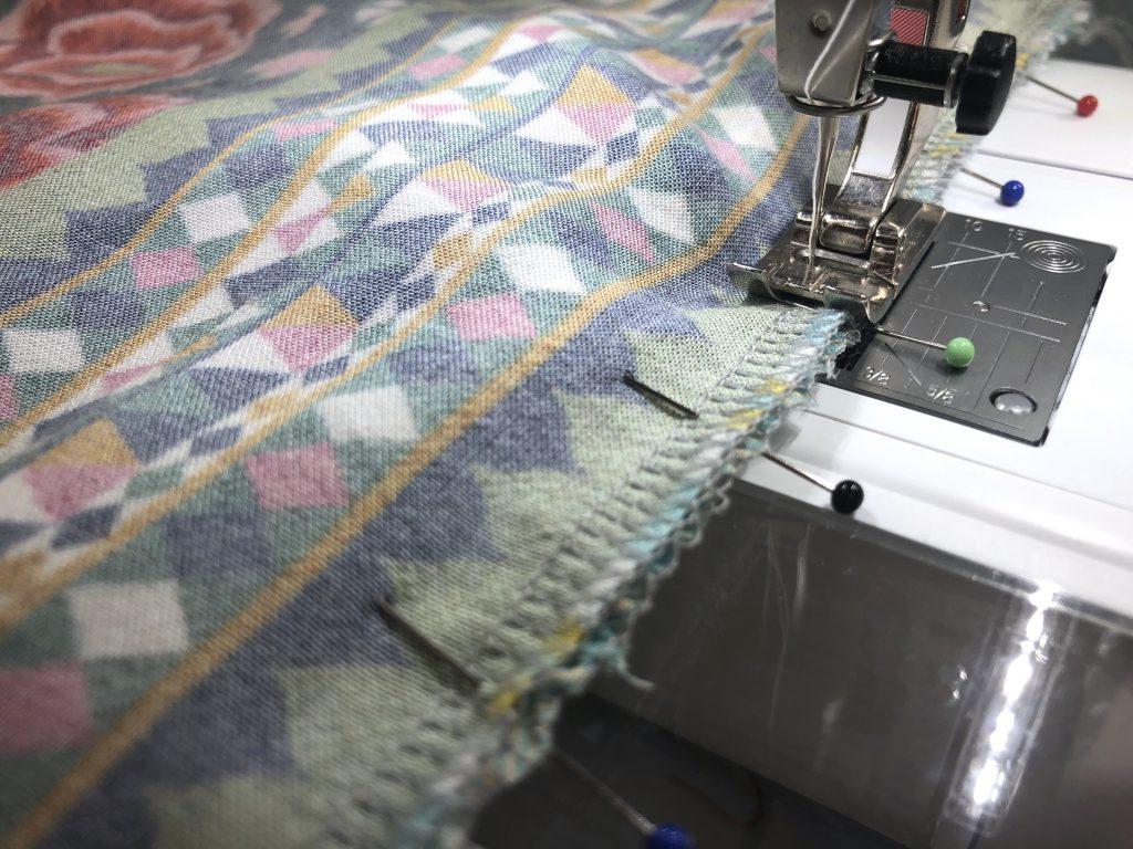 Bild zeigt wie die beiden Stofflagen an der Nähmaschine zusammengenäht werden.
