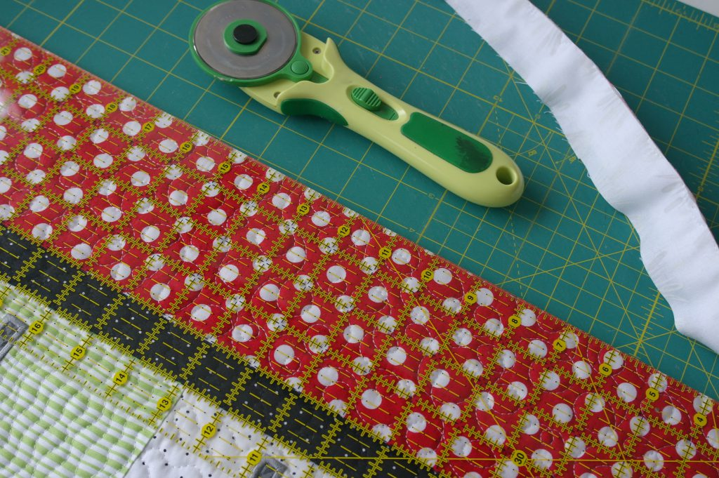 De brede randen afsnijden om zo de quilt recht te maken