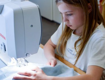 kinderen achter de naaimachine